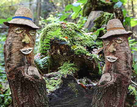 Dead tree stumps turned into faces wearing hats.