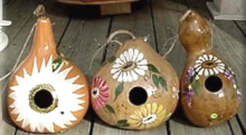 3 decorative Gourds. The designs are very floral or one of a white looking sun.